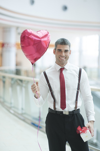 Businessman holding heart shaped balloon and presentの写真素材 [FYI03646891]