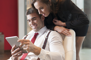 Businesswoman looking over male colleagues shoulder pointingの写真素材 [FYI03646905]