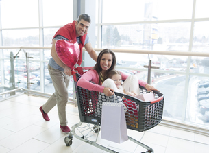 Father pushing mother and young daughter in shopping trolleyの写真素材 [FYI03646921]