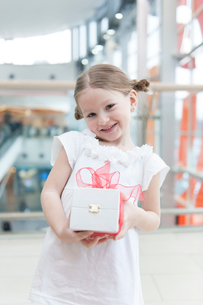 Young girl holding present wrapped in big red bowの写真素材 [FYI03646938]