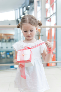 Young girl unwrapping ribbon on presentの写真素材 [FYI03646939]