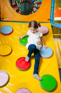 Young girl climbing down ramp in soft play centreの写真素材 [FYI03646956]