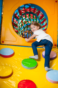 Young girl climbing up ramp into tunnel at soft play centreの写真素材 [FYI03646958]