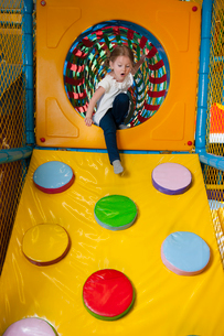 Young girl climbing down ramp in soft play centreの写真素材 [FYI03646959]