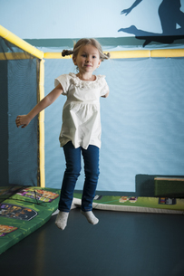 Young girl in mid air on trampolineの写真素材 [FYI03646966]