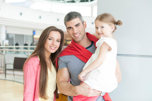 Father and mother pose with young daughter in shopping mallの写真素材 [FYI03646984]