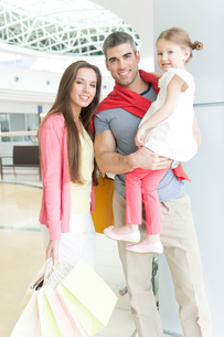 Father and mother pose with young daughter in shopping mallの写真素材 [FYI03646985]