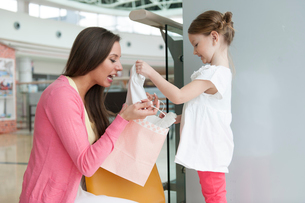 Mother giving daughter gift from paper shopping bagの写真素材 [FYI03646988]