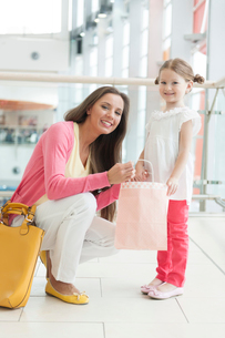 Mother giving daughter paper shopping bagの写真素材 [FYI03646991]
