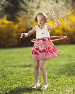 Young girl using hula hoop in a parkの写真素材 [FYI03647011]