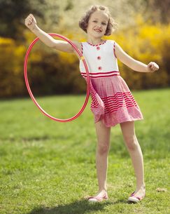 Young girl using hula hoop on arm in a parkの写真素材 [FYI03647012]