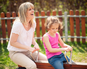Mother and daughter ride seesaw togetherの写真素材 [FYI03647024]