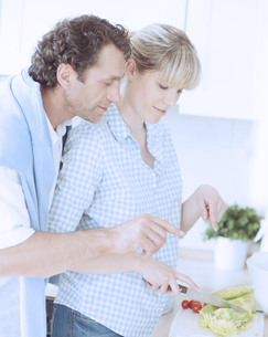 A couple making a healthy salad in the kitchenの写真素材 [FYI03647034]