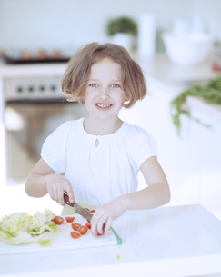 Young girl chopping tomatoes and making a salad in the kitchの写真素材 [FYI03647036]