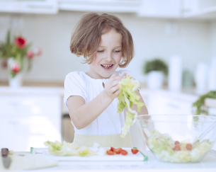 Young girl placing lettuce in salad bowlの写真素材 [FYI03647042]