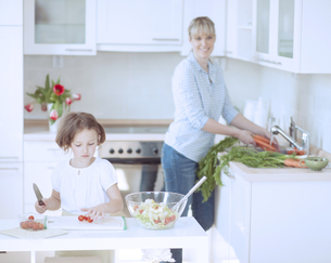 Mother and Daughter (8-9) preparing healthy meal in kitchenの写真素材 [FYI03647048]