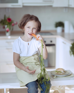Young girl eating carrotの写真素材 [FYI03647050]