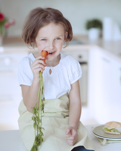 Young girl eating carrotの写真素材 [FYI03647051]