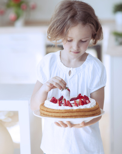 Young girl with cake and strawberriesの写真素材 [FYI03647055]