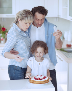 Family preparing healthy meal in kitchenの写真素材 [FYI03647062]