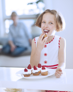 Young girl eating cup cakeの写真素材 [FYI03647076]
