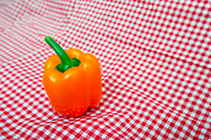 Orange Bell Pepper against red and white chequered clothの写真素材 [FYI03647093]