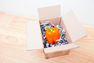 Orange bell pepper wrapped up in a boxの写真素材 [FYI03647100]