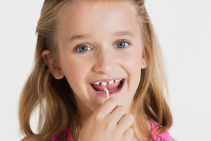 Portrait of young girl flossing teeth against gray backgrounの写真素材 [FYI03647115]