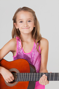 Portrait of young girl playing guitar against gray backgrounの写真素材 [FYI03647119]