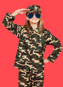Portrait of young girl in military uniform saluting againstの写真素材 [FYI03647125]