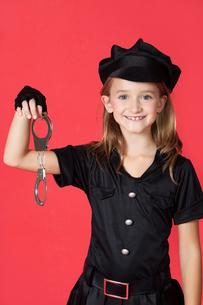 Portrait of young girl in police costume holding handcuffs aの写真素材 [FYI03647128]
