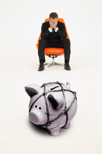 Worried businessman on chair and piggybank tied with rope reの写真素材 [FYI03647137]