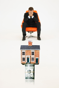 House on top of roll of bills with worried businessman on chの写真素材 [FYI03647138]