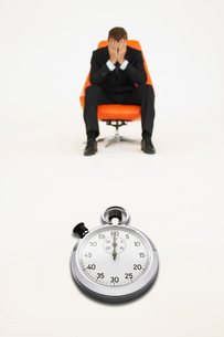 Worried businessman sitting on chair with stopwatch represenの写真素材 [FYI03647139]