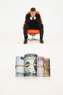 Money rolls with worried businessman on chair representing fの写真素材 [FYI03647141]