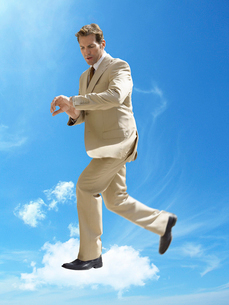 Business running whilst checking wristwatch in mid-air againの写真素材 [FYI03647142]