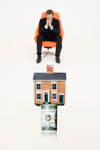 House on top of roll of bills with pensive businessman on chの写真素材 [FYI03647143]