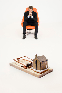 Model home on mouse trap with worried businessman sitting onの写真素材 [FYI03647147]