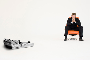 Wad of cash on mouse trap with pensive businessman on chairの写真素材 [FYI03647148]