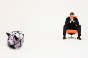 Pensive businessman on chair and piggybank tied with rope reの写真素材 [FYI03647150]