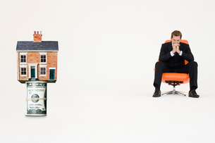 House on top of roll of bills with pensive businessman on chの写真素材 [FYI03647151]