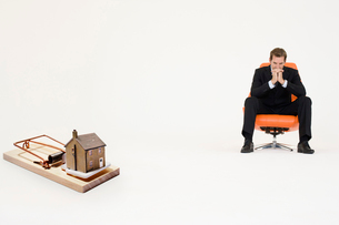 Model home on mouse trap with worried businessman sitting onの写真素材 [FYI03647152]