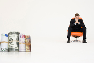 Money rolls with pensive businessman on chair representing fの写真素材 [FYI03647153]
