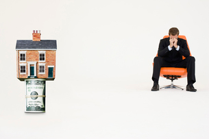 House on top of roll of bills with worried businessman on chの写真素材 [FYI03647156]