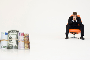 Money rolls with worried businessman on chair representing fの写真素材 [FYI03647157]