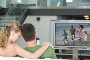 Rear view of young couple watching television in living roomの写真素材 [FYI03647167]