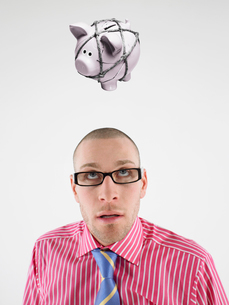 Young businessman looking up at piggy bank tied with rope reの写真素材 [FYI03647174]