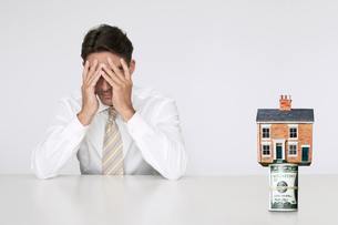 Worried businessman at table with house on top of bills reprの写真素材 [FYI03647179]