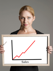 Portrait of young businesswoman showing sales graph againstの写真素材 [FYI03647183]