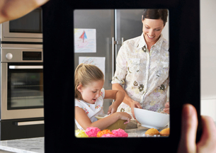 Female hand framing mother and daughter baking together in kの写真素材 [FYI03647190]